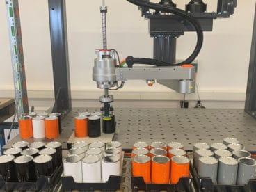 Bilden von Mischtrays: Robotergreifer bestückt Trays mit Dosen